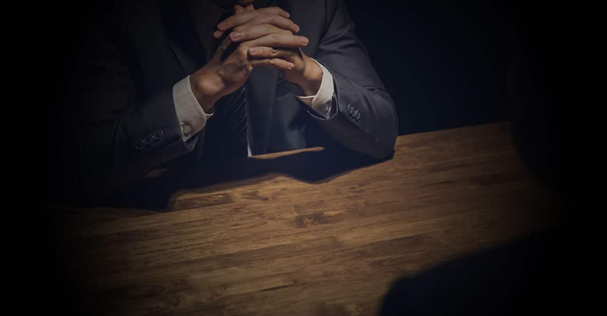 Mann sitzt einer unkenntlichen Person gegenüber und hat die Finger verschränkt.