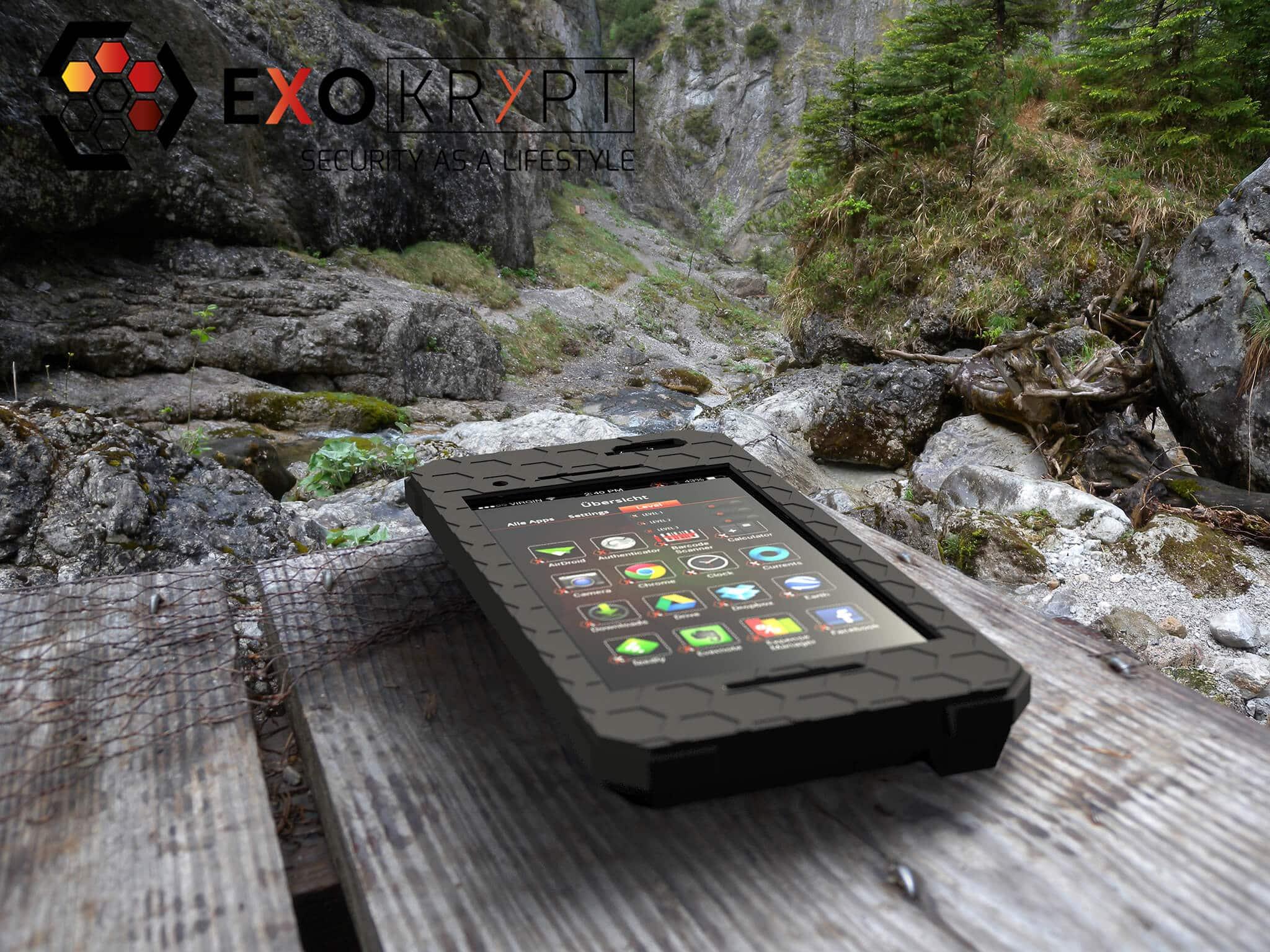 """ExoShield """"THE EDC"""" - Outdoor Hülle in Schwarz auf einem Holztisch vor einer Schlucht liegend"""