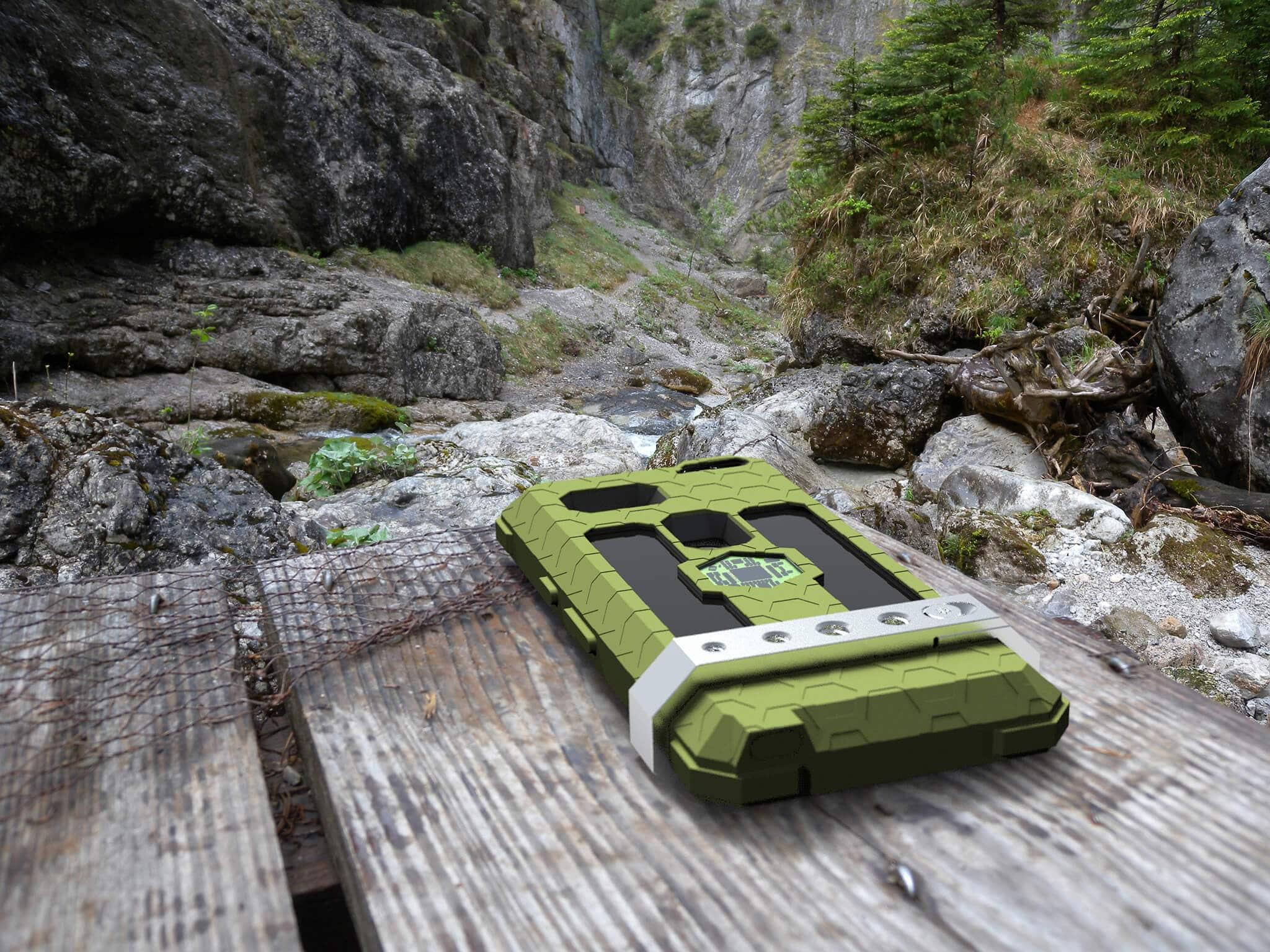 """ExoShield """"THE EDC"""" - Outdoor Hülle in Olive - Inlets Schwarz - Universal Mount aus Metall auf einem Holztisch vor einer Schlucht liegend"""