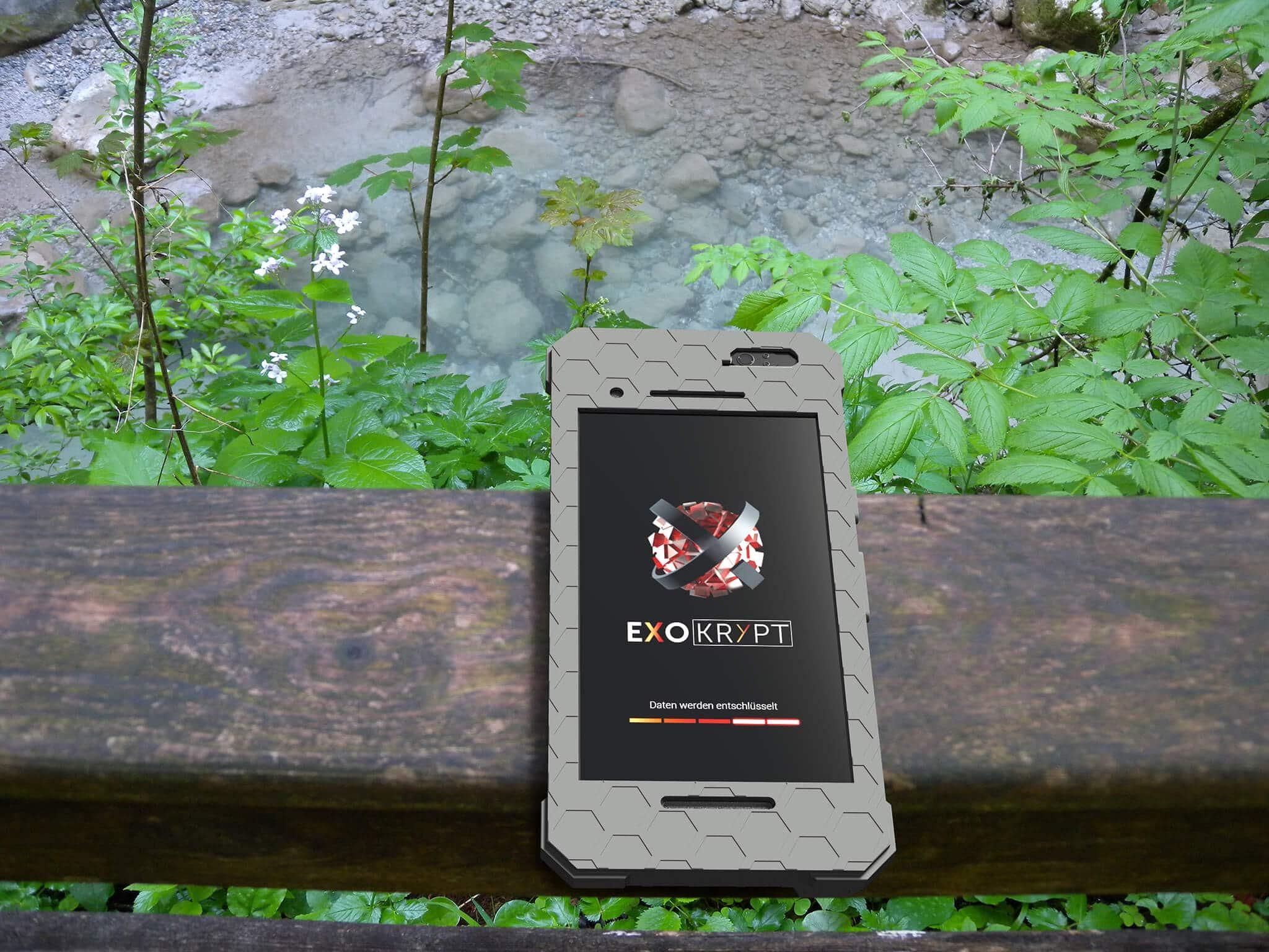 """ExoShield """"THE EDC"""" - Outdoor Hülle in Grau auf einem Brückengeländer aus Holz liegend"""